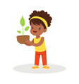 sweet little girl standing and holding a plant in vector image vector image
