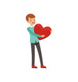 smiling teen boy holding red heart happy vector image vector image