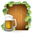 beer mug and hops branch on a wooden background vector image