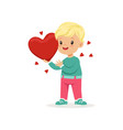 sweet little boy holding red heart happy vector image vector image