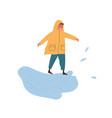 funny boy in raincoat playing in puddle enjoying vector image vector image