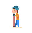 skiing man in an orange jacket and blue hat vector image