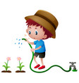 Boy watering plants with hose
