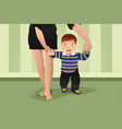 mother helping her baby boy learning to walk vector image