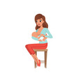 young mother sitting on a chair and breastfeeding vector image