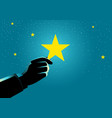 businessman hand picking up a star vector image vector image