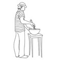 young man in hat and striped t-shirt prepares food vector image vector image