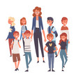 smiling female teacher standing with group of vector image vector image