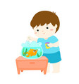 cute little boy feeding fish in aquarium cartoon vector image vector image