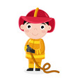 smiling little boy in fireman uniform with hose vector image vector image