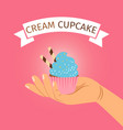 hand holding blue cream cupcake vector image vector image