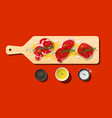 raw beef steaks and seasoning on cutting board vector image vector image