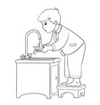boy stands on a stool and washes his hands under vector image vector image