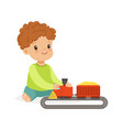sweet little boy playing playing with toy railway vector image