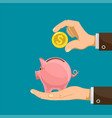 hand puts a golden dollar coin into a piggy bank vector image