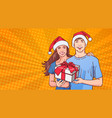 couple wearing santa hats hold gift happy man and vector image vector image